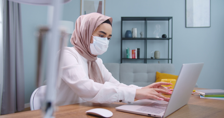 Middle plan of sick young businesswoman in hijab wearing face mask typing on computer, searching in Internet at home office. Muslim female working distantly self-isolating having coronavirus symptom. Royalty-Free Stock Footage #1059410747