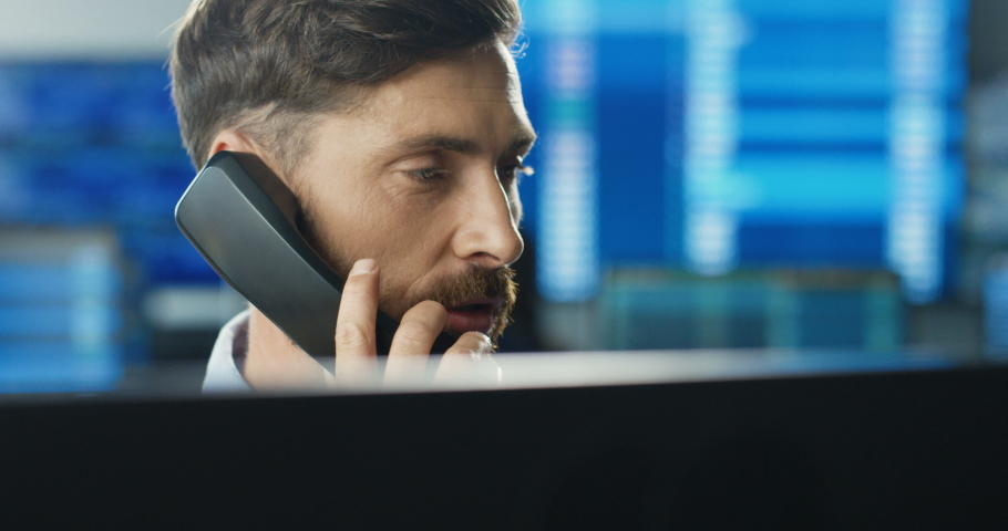Close up of Caucasian male broker working at computer in trading office and answering phone calls on many telephones. Trader buying and selling while talking with clients and working at stock market. Royalty-Free Stock Footage #1059455855