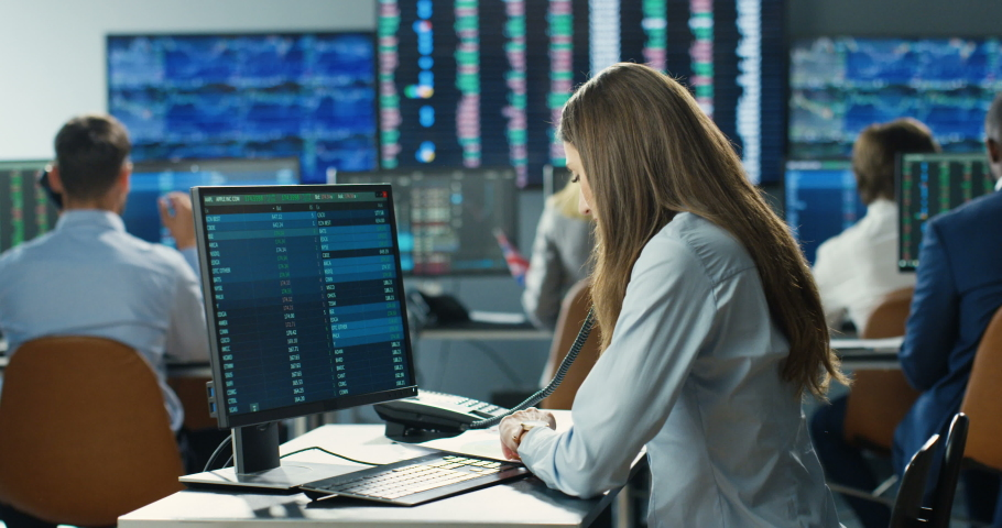 Caucasian woman broker sitting in front of computer monitor with numbers and talking on telephone. Female trader buying and selling stocks. Analyzing market. Speaking on phone with client. Royalty-Free Stock Footage #1059455876