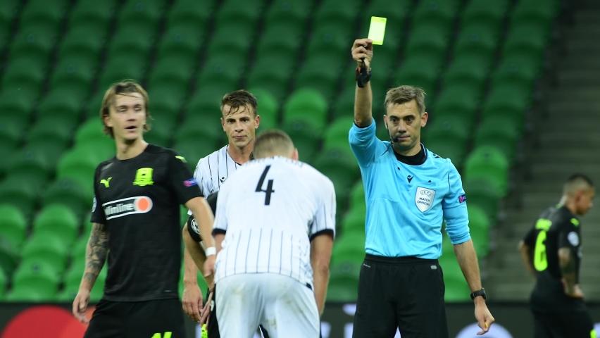 Krasnodar, Russia - September 22, 2020 : Football match FC Krasnodar (Russia) vs FC PAOK (Greece) - 2020/2021 UEFA Champions League - Playoff Round 1 match, referee showing 2 yellow cards