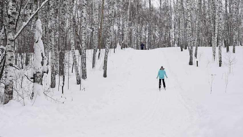 The girl is skiing down the mountain in winter, falls and laughs. Winter sports. Skiing.