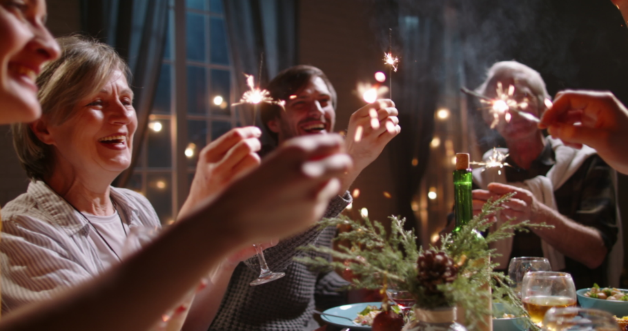 Large happy caucasian family celebrating christmas or new year together, holding sparklers at party dinner table and making wishes - celebration concept 4k footage Royalty-Free Stock Footage #1059465260