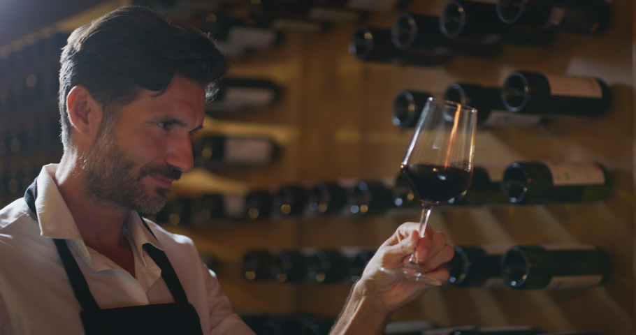 Authentic shot of happy successful male winemaker is tasting a flavor and checking red wine quality poured in transparent glass  in a wine cellar.