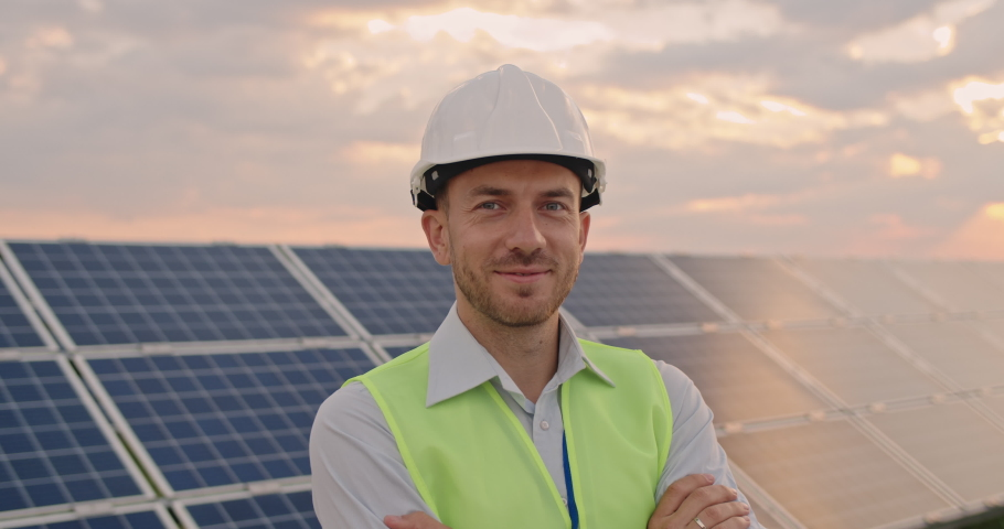 Portrait of happy male engineer in protective helmet crossing arms while looking to camera. Handsome man in uniform smiling while standing at solar power farm. Concept of green energy Royalty-Free Stock Footage #1059465863
