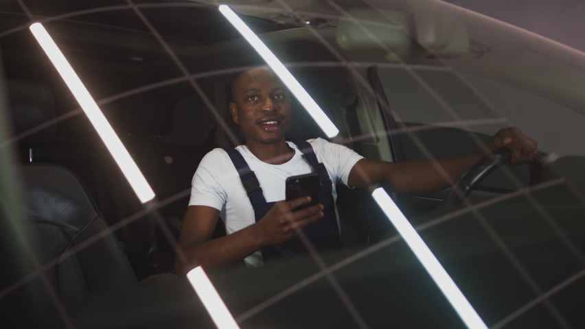 Handsome african american man driving an expensive car with a phone in his hands, shooting through the glass, in the garage | Shutterstock HD Video #1059467198