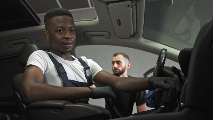 African american came to work, helps to wash car interiors, cheerful young man helps to clean car interior, two workers at work in the garage | Shutterstock HD Video #1059467270