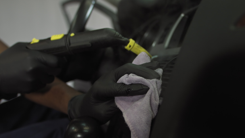 African american student at work, steaming car dashboard from bacteria and viruses, cleaning interior from dust and germs, shooting in car interior | Shutterstock HD Video #1059467294