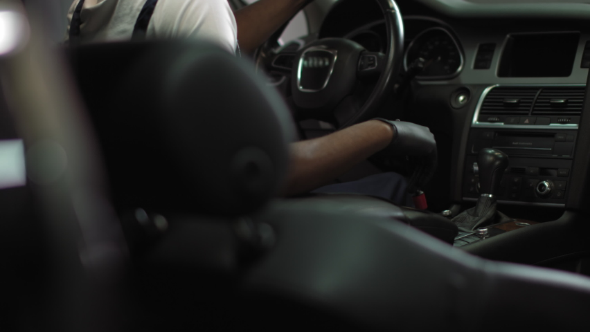African american sitting in the cabin of an expensive car and brushing the interior, a young man in special clothes at work, working with cars | Shutterstock HD Video #1059467315