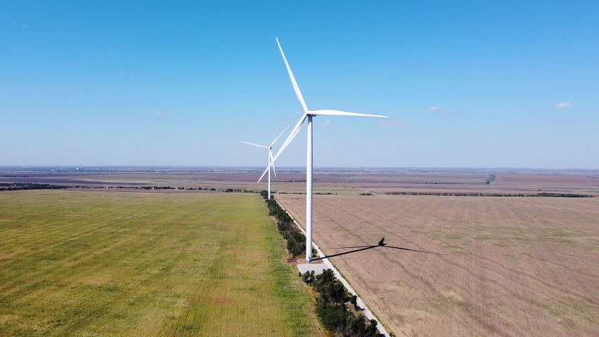 Two wind turbines aerial footage at southern ukrainian wind farm with green field and blue sky | Shutterstock HD Video #1059467690