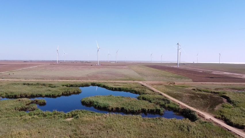 Aerial footage of a wind farm landscape with lake in front of energy converters at autumn in Ukraine | Shutterstock HD Video #1059468005