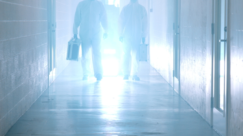 Laboratory Workers Walking in Corridor. Laboratory workers with Cases in Hands Wearing Chemical Suit and Masks | Shutterstock HD Video #1059468224