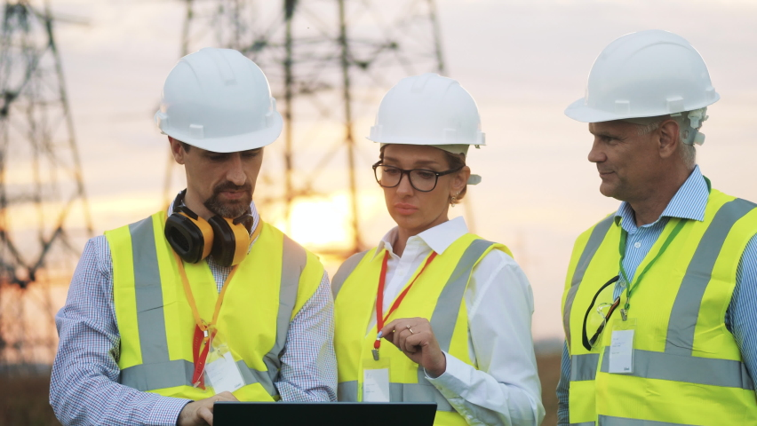 Engineers in uniform work with laptop, standing on field with power lines. | Shutterstock HD Video #1059468449