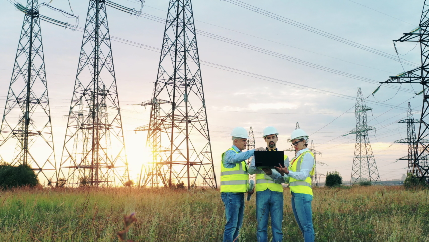 Electric industry, electrical energy production concept. Energy workers discuss work near power lines. | Shutterstock HD Video #1059468461