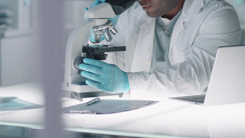 Modern African American man wearing protective gloves and eyewear doing medical tests using microscope in laboratory | Shutterstock HD Video #1059468779