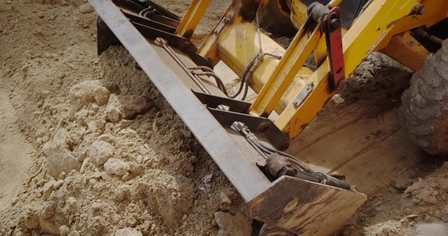 The blade of a bulldozer digging the ground close-up