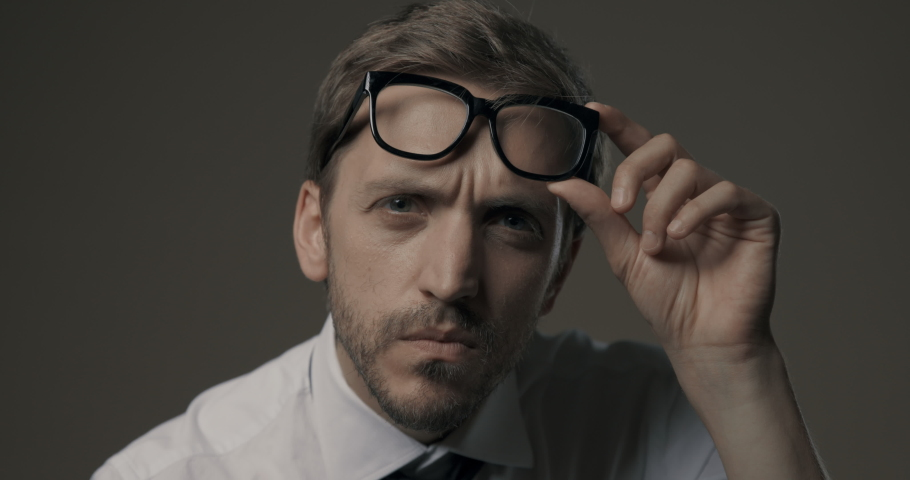 Man staring at camera and holding glasses, he is confused and has vision problems Royalty-Free Stock Footage #1059484430