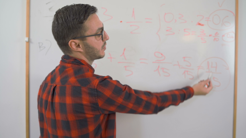 Close shot of young man math teacher with red shirt and glasses writing complex math equations on whiteboard Royalty-Free Stock Footage #1059485348