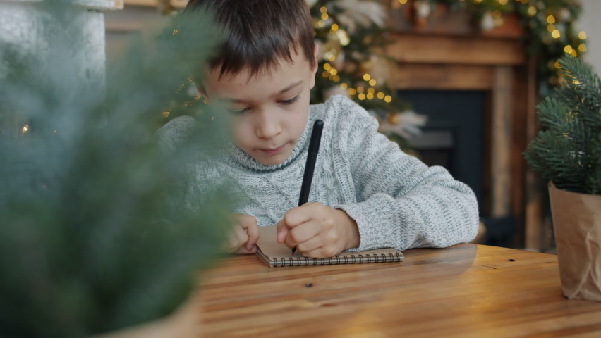 Portrait of thoughtful little boy writing letter to Santa Claus before Christmas in decorated room, child is sitting at table alone. New Year and holidays concept.