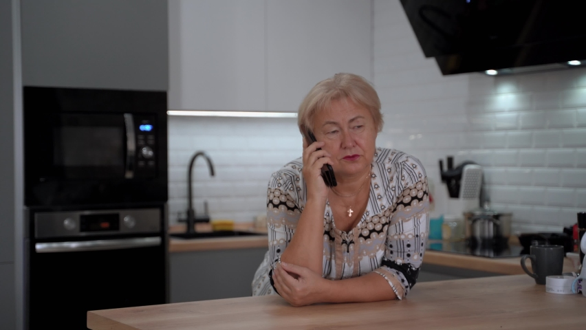 This video shows an elderly woman talking on the phone at home.