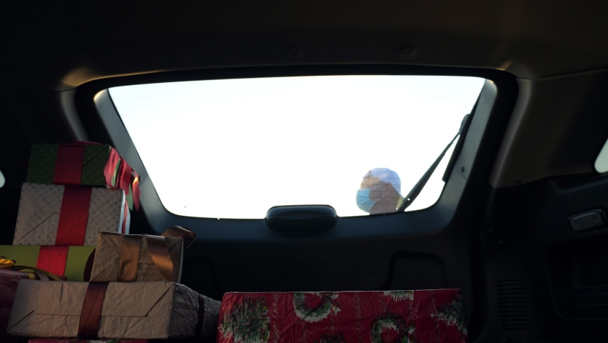 delivery service. deliveryman in protective mask. courier loads boxes. gift boxes in car. beautifully wrapped parcels. view from inside the car. donation, charity or delivery concept. Royalty-Free Stock Footage #1059495812