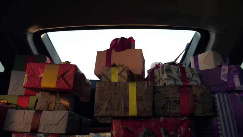 delivery service. deliveryman in protective mask. courier unloads boxes. gift boxes in car. beautifully wrapped parcels. view from inside the car. donation, charity or delivery concept. Royalty-Free Stock Footage #1059495821