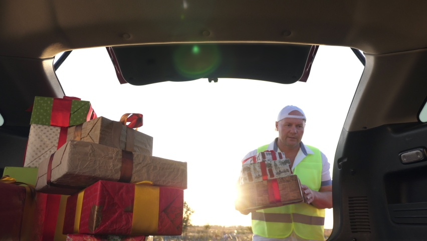 delivery service. deliveryman loads boxes. gift boxes in car. beautifully wrapped parcels. view from inside the car. donation, charity or delivery concept. Royalty-Free Stock Footage #1059495827