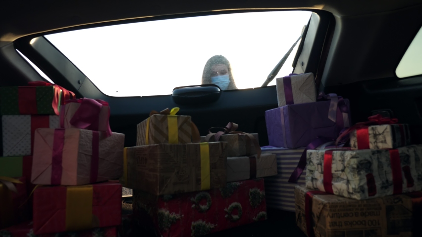 gift boxes in car. woman, in protective mask, unloads many beautifully wrapped boxes, from car trunk. view from inside the car. donation, charity or delivery concept. Royalty-Free Stock Footage #1059495833