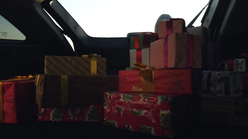 Gift boxes in the car. a woman unloads many beautifully wrapped, packed boxes, from car trunk. view from inside the car. donation, charity concept. delivery of gifts, parcels
