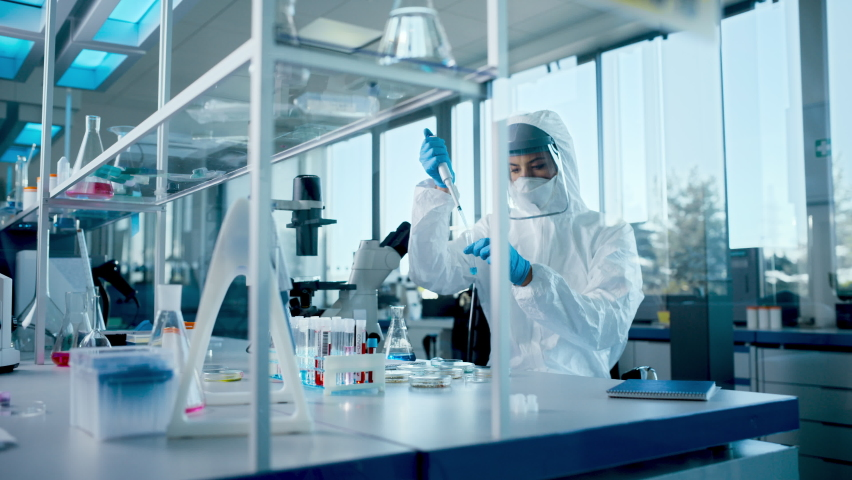 Beautiful Female Medical Scientist Wearing Coverall and Face Mask Using Micro Pipette while Working with Test Tubes. Vaccine, Drugs Research and Development Innovative Laboratory, Modern Equipment   Shutterstock HD Video #1059497930