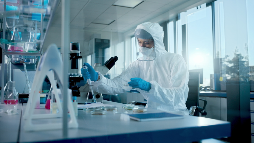 Beautiful Female Medical Scientist Wearing Coverall and Face Mask Using Micro Pipette while Working with Petri Dish. Vaccine, Drugs Research and Development Laboratory with Modern Equipment