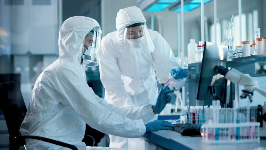 Medical Laboratory: Team of Microbiology Scientists Wearing Sterile Coveralls, Face Shields and Masks Talk, Use Computer to Analyse Test Tube Blood Samples and Develop Vaccine, Drugs and Antibiotics