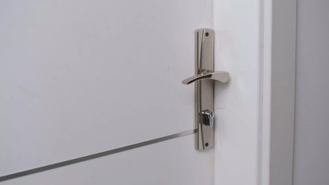 The man opens the door of the room with the key.