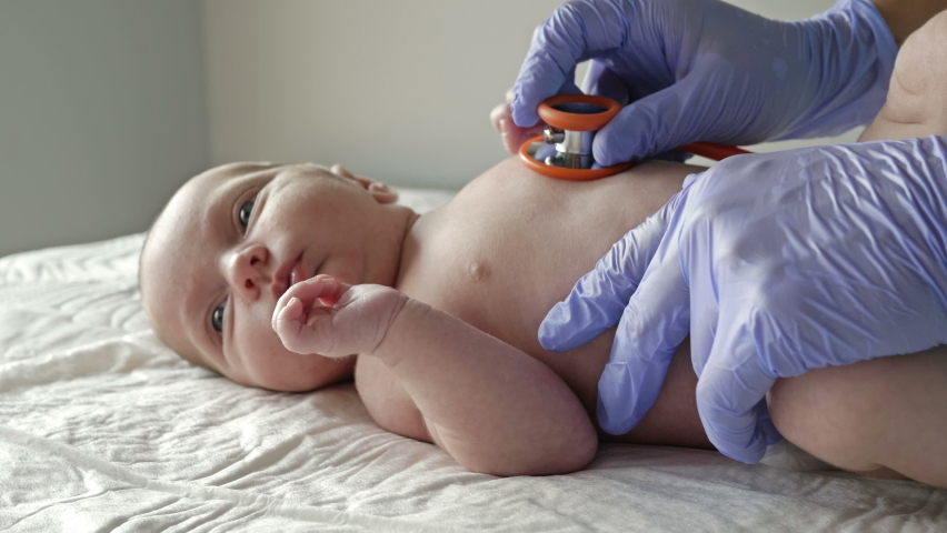 Neonatologist in latex gloves examines a newborn baby with a stethoscope. Close-up.