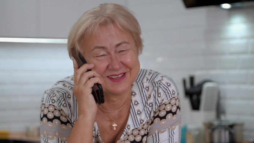 This video shows an elderly woman talking on the phone at home. Close-up.