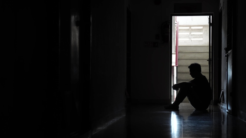 Silhouette of a sad man sitting in the dark leaning against the wall in old condo, Domestic violence, family problems, Stress, violence, The concept of depression and suicide