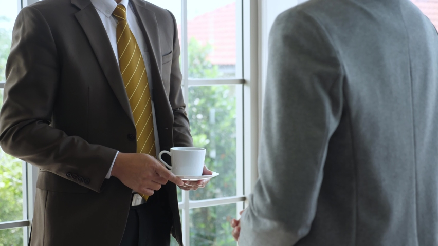 Business deal during coffee break concept. Handheld, close up shot of 2 anonymous professional businessmen in formal suit discussing business deal and shaking hand