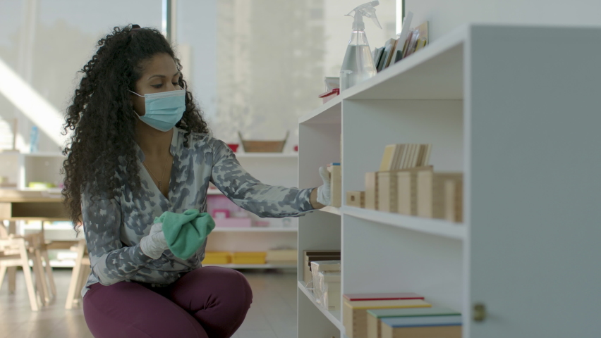 Back to school cleaning. A teacher sanitizes her classroom in preparation for students return during a pandemic. Shot in 4k. Royalty-Free Stock Footage #1059526850