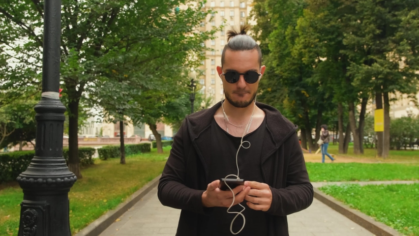 A young Caucasian charismatic brunette guy in dark clothes and sunglasses moves to the music along the park alley. A man listens to music on his smartphone through white wired headphones.