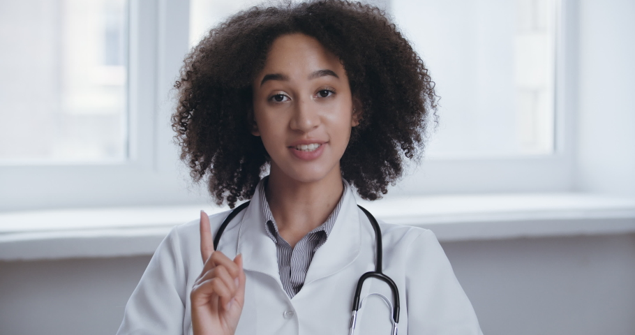 Young professional african woman doctor wear uniform with stethoscope talk conference video call consult patient online looking at camera webcam, distant medical consultation in internet in qurantine | Shutterstock HD Video #1059532811