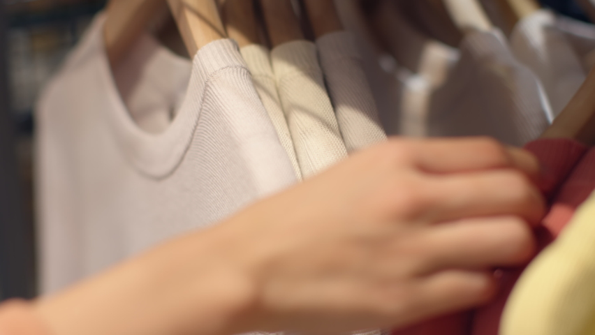 Close-up of female hands plucked hanger Choosing clothes in a clothing store. woman hand runs across a rack of clothes buying Clothes in a shopping mall. Sale Promotion and Shopping Concept. Royalty-Free Stock Footage #1059540842