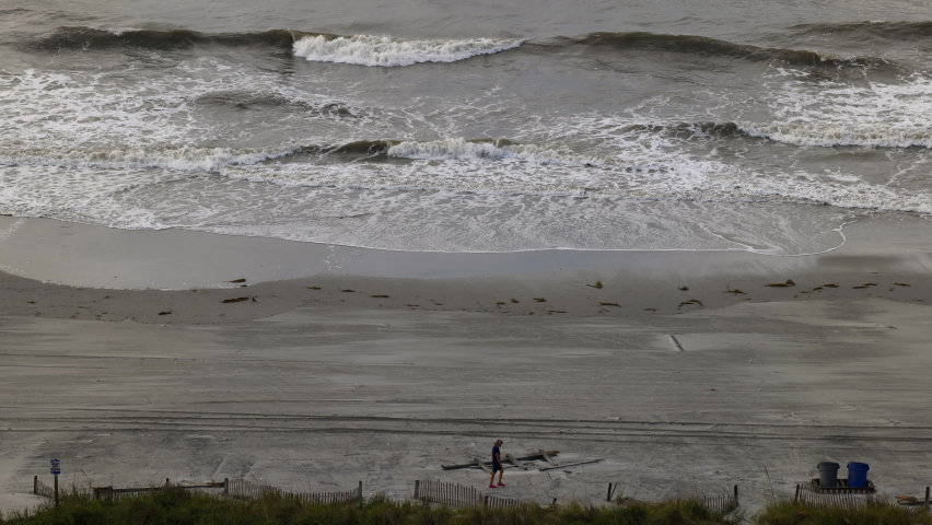 Man walking on a beach just before hurricane hits. Shot during the calm before the Hurricane Isaias arrived at North Myrtle Beach, South Carolina, U.S., on August 3, 2020.