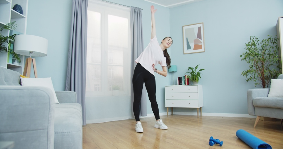 Middle plan of sporty woman training morning workout in home interior. Young female doing gym workout in home. Sport person doing leaning to the right and left, warm-up. Healthy and sport lifestyle. Royalty-Free Stock Footage #1059554069