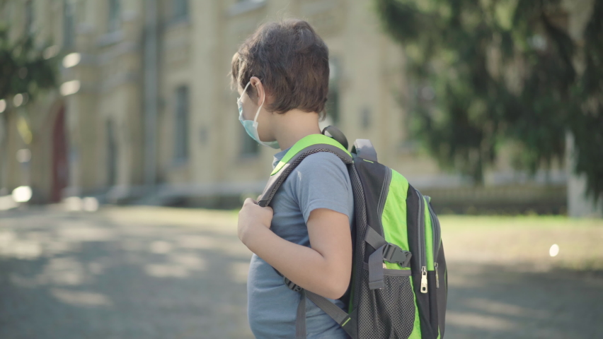 Sad schoolboy with backpack in face mask turning to camera. Portrait of upset Caucasian boy standing on sunny schoolyard. Cute brunette kid studying in middle school during Covid-19 pandemic. Royalty-Free Stock Footage #1059555734