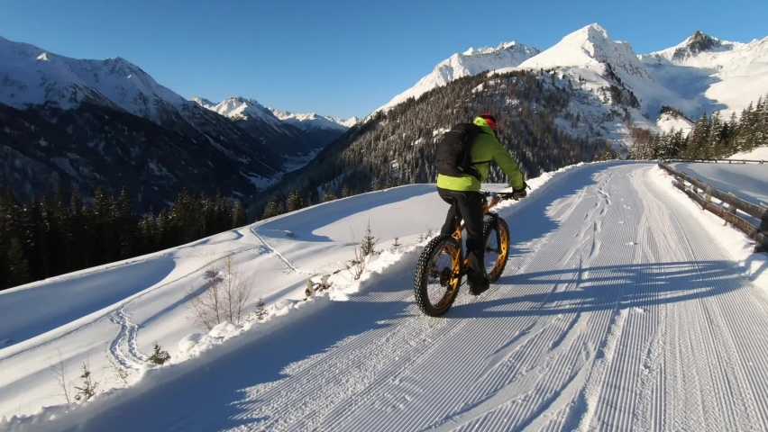 MTB Mountainbiking in the snow. Biking with MTB high up in the mountains in Winter. Fatbike tour with a guide. Beautiful mountain view Tirol.