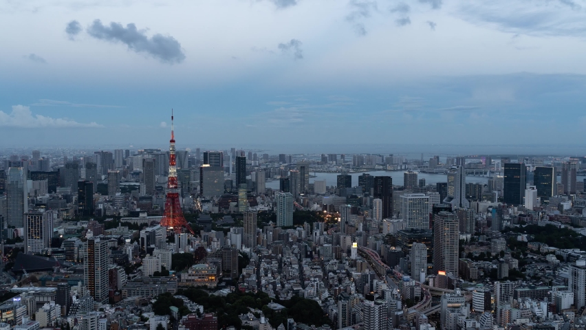 Beautiful 4k Timelapse over Tokyo cityscape at dusk illumination lighting up Tokyo Tower - Zoom In
