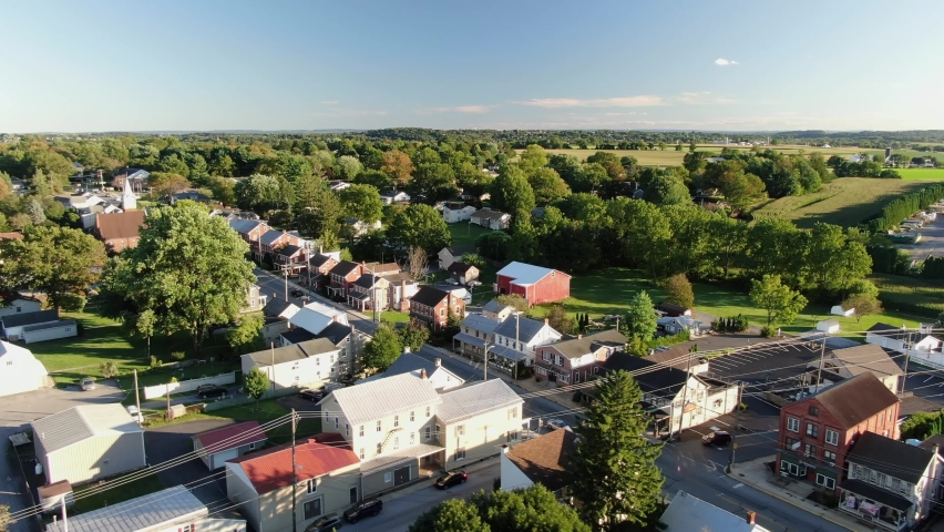 High and wide aerial overhead shot of small American town, village, establishing shot shows homes and housing along street, green trees and farmland in distance during August, North America, USA Royalty-Free Stock Footage #1059565757