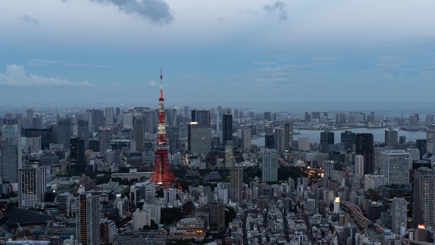 Beautiful 4k Timelapse over Tokyo cityscape at dusk illumination lighting up Tokyo Tower - Panning Shot