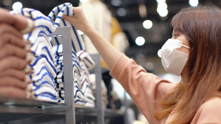 Young Asian woman wearing a medical face mask chooses clothes in a clothing store during coronavirus pandemic in department store. Store Re-opening Female Customer Choosing clothes after quarantine.     Shutterstock HD Video #1059570563