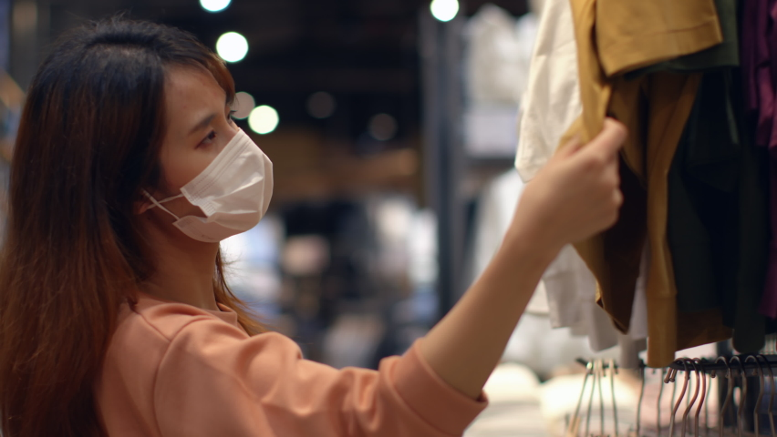 Young Asian woman wearing a medical face mask chooses clothes in a clothing store during coronavirus pandemic in department store. Store Re-opening Female Customer Choosing clothes after quarantine.     Shutterstock HD Video #1059570572