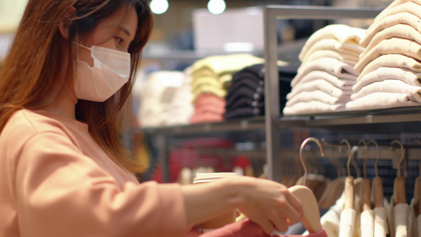 Young Asian woman wearing a medical face mask chooses clothes in a clothing store during coronavirus pandemic in department store. Store Re-opening Female Customer Choosing clothes after quarantine.     Shutterstock HD Video #1059570575